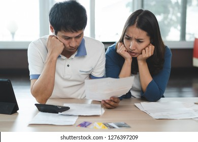 Family financial crisis concept. Stressed couple calculating credit card debt.
