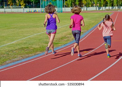 Family fitness, active mother and kids running on stadium track, back view, training with children sport concept