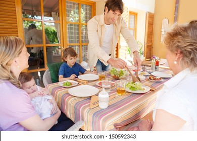 Family of five gathering around a table with food preparing to have lunch, with the father serving green salad during a sunny day outdoors.
