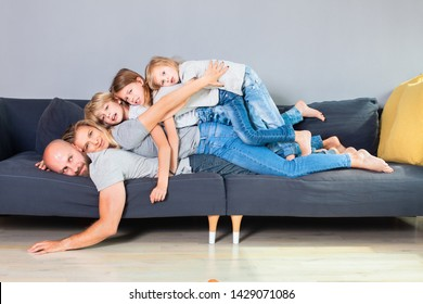 The family of five lie on top of each other while lying across the couch.Happy family stacking on top of each other on the bed.Mother father and children enjoy closeness and spending time together