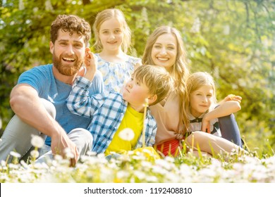 Family of five sitting on a meadow blowing dandelion flowers being happy and playful