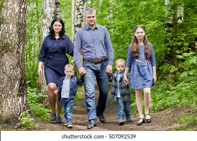 Family of five walks in green summer park.