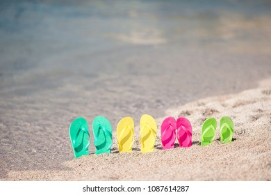 Family flip flops on beach in front of the blue sea. Four flip flops in the sand
