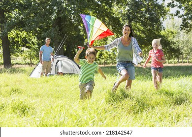 Family Flying Kite Camping Holiday In Countryside