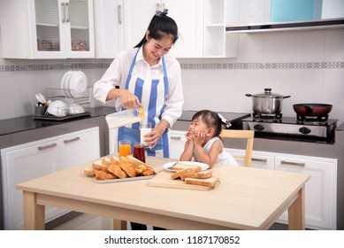 Family, food, breakfast and people's thoughts - happy mom pouring milk from a jug to a cup of coffee and little girl sitting in a baby eating chair at the kitchen at home.