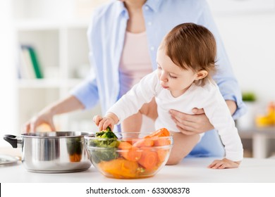 family, food, healthy eating, cooking and people concept - happy mother and little baby girl with vegetables and pot at home kitchen