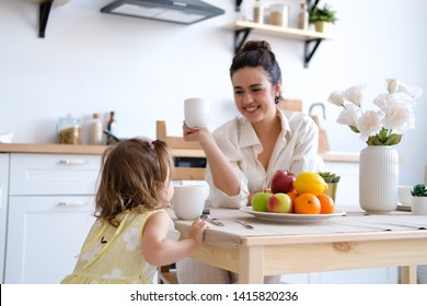 Family, food and people concept - happy mother and daughter having Breakfast at home. Fruit on the table, bright and spacious kitchen. A beautiful young woman and the baby.