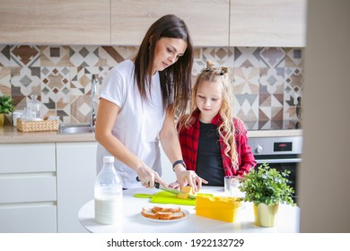 family, food and people concept - happy mother and daughter having breakfast at home