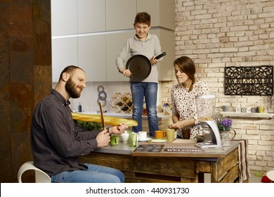Family forming a band in kitchen, pretending to play on instruments.