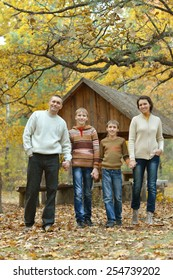 Family of four in autumn forest
