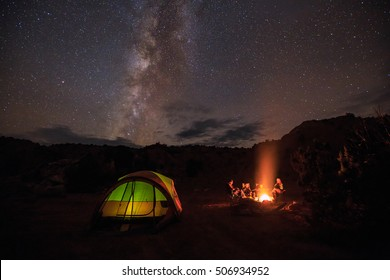 Family of four by a campfire in the Utah desert with stars and the Milky Way, USA.