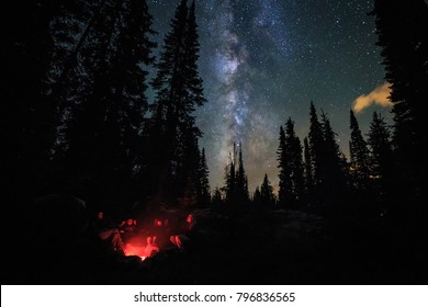 Family of four by a glowing campfire under the Milky Way and stars, Colorado, USA.