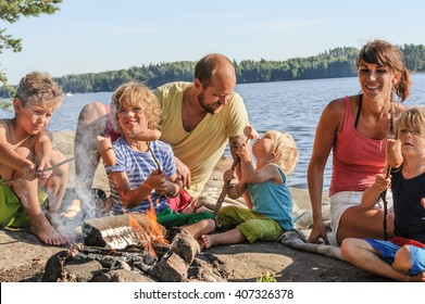 Family with four children grilling sausages over a camp fire beside a lake. The sausages are stuck onto wooden steaks gathered from the forest.