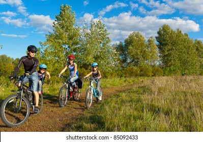 Family of four cycling outdoors. Happy parents with two kids on bikes