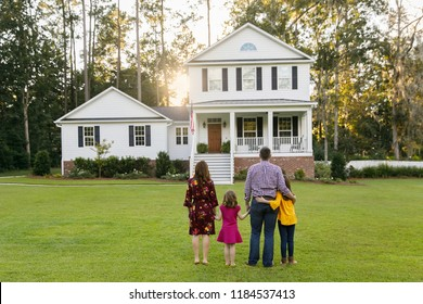 Family of Four with Daughters Looking at their New Construction Farmhouse Home with Curb Appeal