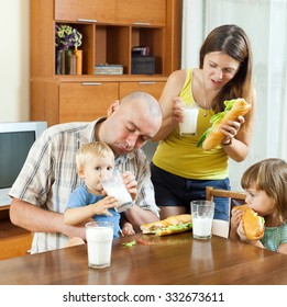 family of four eating sandwiches at home interior