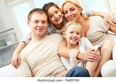 A family of four embracing and smiling at home