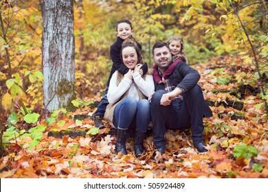 A Family of four enjoying golden leaves in autumn park