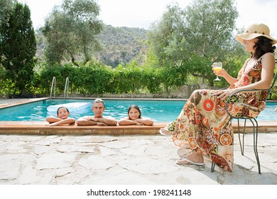 Family of four enjoying a summer holiday break in a vacation home garden with swimming pool, refreshing during a hot day in the water, outdoors. Active family lifestyle and activities together.