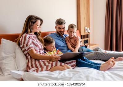 Familie von vier Personen, die zusammen im Hotelzimmer genießen, sitzend auf Bettvorlesung Hotels Angebote.