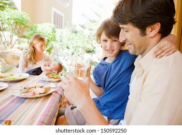 Family of four gathering around a table with food in a home porch garden outdoors with mother, father, baby girl, and a young boy drinking water with dad.