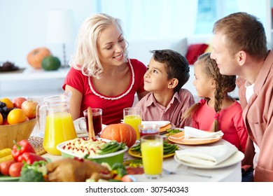 Family of four gathering at dinner table