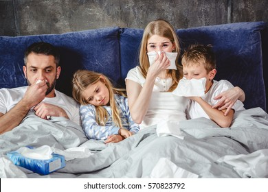 Family of four has a flue and lying on bed together