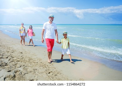 Family of four having fun at the beach on a sunny day