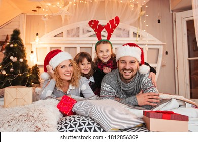 Family of four having fun for Christmas on the bed