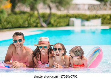 Family of four having fun in the swimming pool together