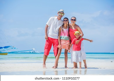 Family of four having fun at the tropical beach