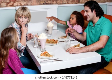 Family of four having great time in a restaurant