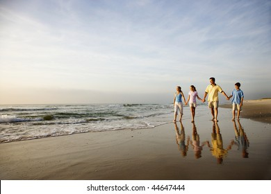 Family of four holding hands and walking on beach in North Carolina.