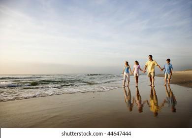 Familie von vier Händen und laufen am Strand in North Carolina.