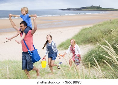A family of four are leaving the beach together. The little boy i on his dads shoulder smiling.