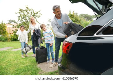 Family of four loading car trunk to leave for vacation