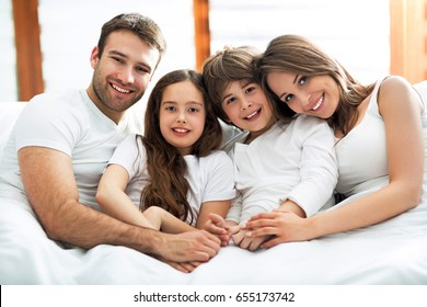 Family of four lying on bed
