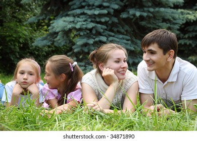 family of four lying on grass and looks on each other