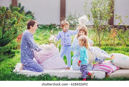 A family of four made a fight on the pillows. Mom, dad, son and daughter are laughing, throwing feathers around from the pillow