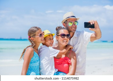 Family of four making selfie and having fun at the tropical beach
