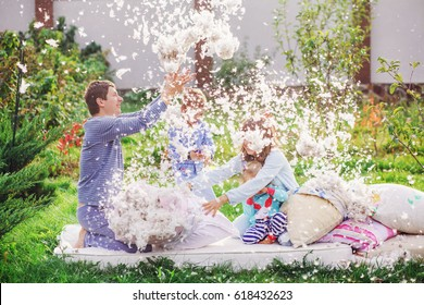 A family of four members arranged a fight on the pillows. Mom, Dad, son and daughter fight with pillows, and feathers fly around