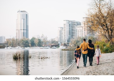 A family of four: mom dad and two daughters walk along the river bank hugging each other. Happy family