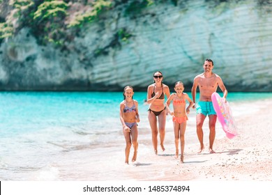 Family of four on the beach having fun. Kids and parents run on the seashore