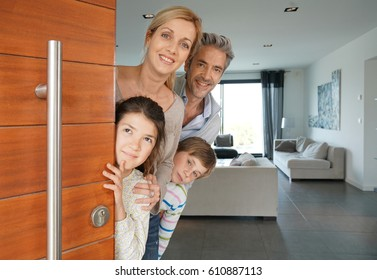 Family of four opening house front door