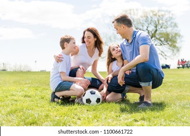 Family of four outdoors in a field having fun