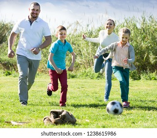 caucasian family of four people happily playing in football together outdoors