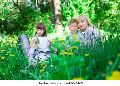 A family of four people having fun in the park. Green grass and yellow dandelions.