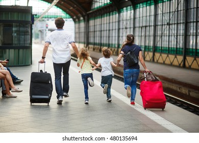 Family of four people rushes on platform of railway train station. They are late for a train. Mum holds the son by the hand, the daddy - the daughter. Adults roll greater suitcases.