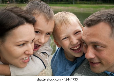 family of four people in a summer park