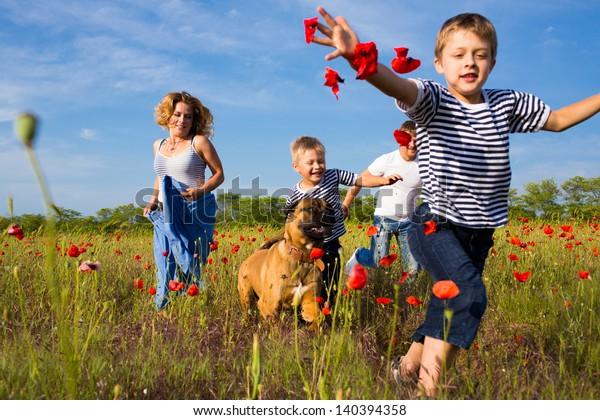 Familie von vier Personen, die auf dem Mohnfeld spielen